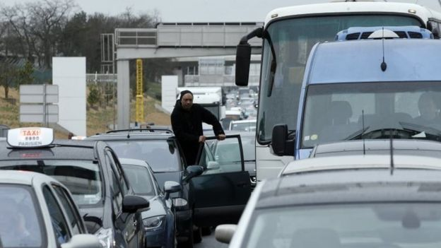 A man watches the traffic on the highway leading to the Orly airport (18 March 2017)