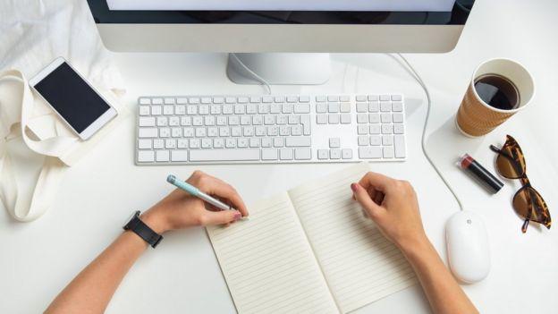 Una persona escribiendo con la mano izquierda frente a una computadora.