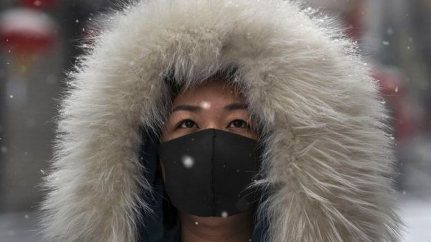 A woman wears a protective mask during a snowfall in Beijing