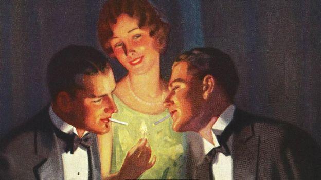 Mulher acende chama para homens fumarem