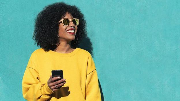 Jeune femme avec un pull jaune vif tenant un smartphone, posant devant un mur turquoise.