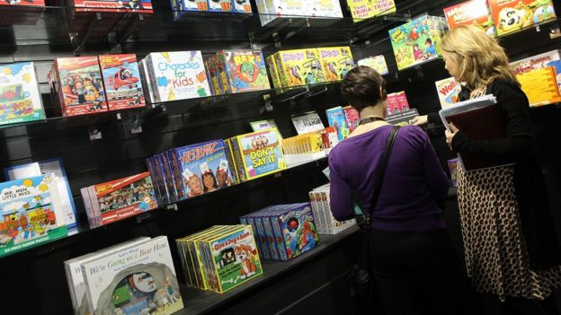 Two women looking at games on a shelf