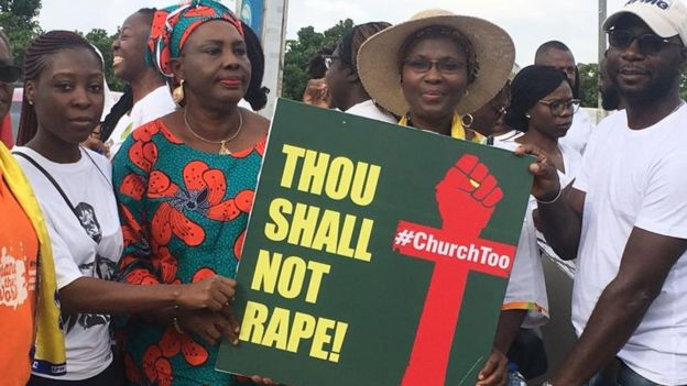People holding up a placard saying Thou Shall Not Rape