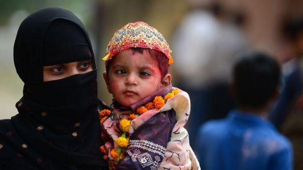इलाहाबाद में सेरेब्रल पाल्सी से पीड़ित बच्चों के लिए त्रिशला फाउंडेशन के आयोजित होली जश्न समारोह में अपने बच्चे को शामिल कराने ले जाती एक मुस्लिम महिला (25 फरवरी 2018)