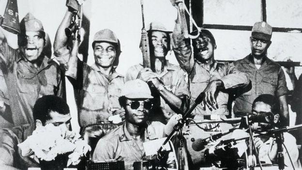 Em foto de 1980, o presidente da Libéria, Samuel K. Doe (óculos escuros), aparece cercado por membros de seu Conselho de Redenção dos Povos