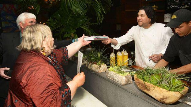 El chef peruano Gastón Acurio alcanza un libro a una pareja.