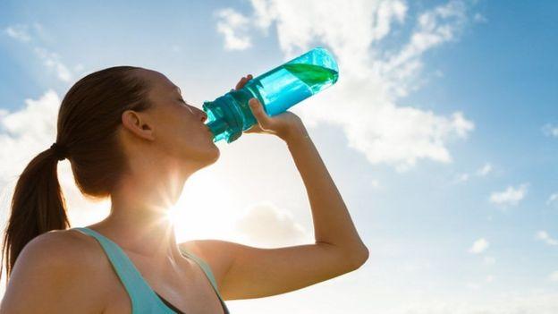 Mulher bebe água após exercício físico