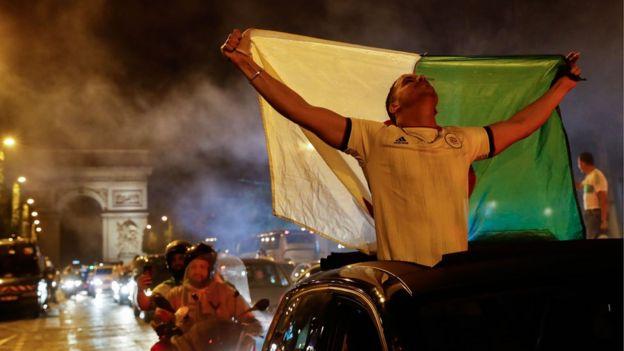 محتفلون وسط جادة الشانزيليزية في العاصمة الفرنسية باريس بفوز المنتخب الجزائري