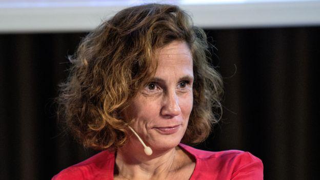Ilaria Capua sentada, com microfone perto do rosto, em evento