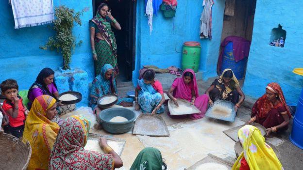 Mujeres preparan comida en el piso de un patio.