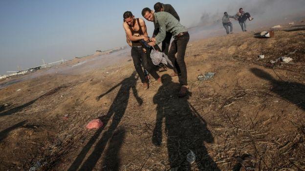 Palestino ferido em Gaza sendo carregado