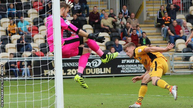 Rhys Healey heads the ball past Cambridge goalkeeper Will Norris