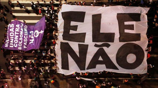 """Vista aérea de manifestantes en Sao Paulo con telones que dicen """"EleNão""""."""