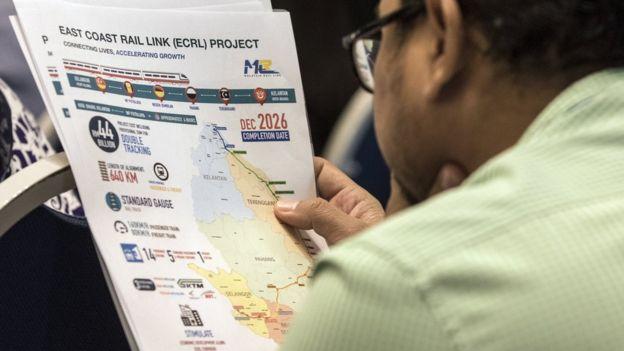 马哈蒂尔记者招待会之前,记者正在看有关东铁项目的介绍资料