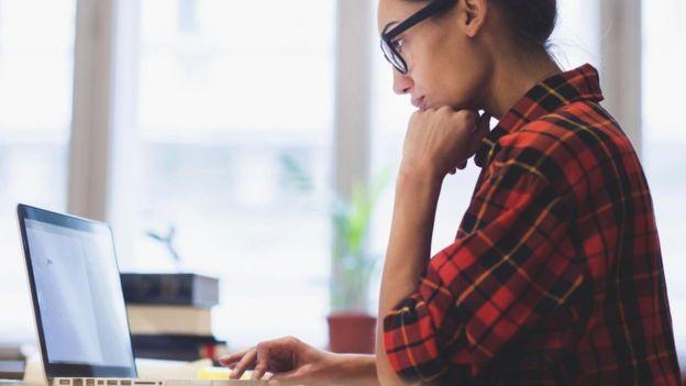 Mujer mira su computadora.