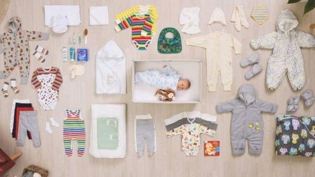 Bebê dentro da caixa de papelão, com seus produtos ao lado