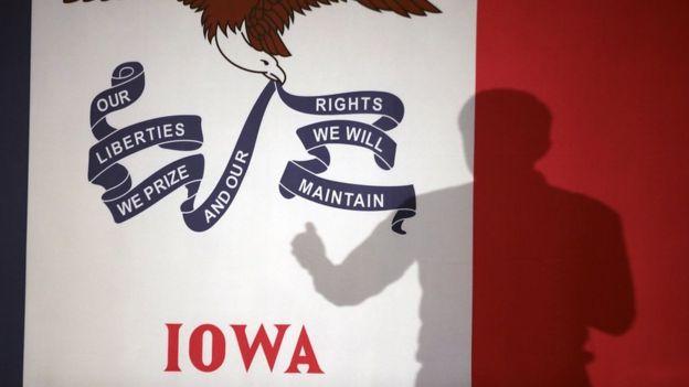 Bandera de Iowa con la sombra de un candidato haciendo campaña