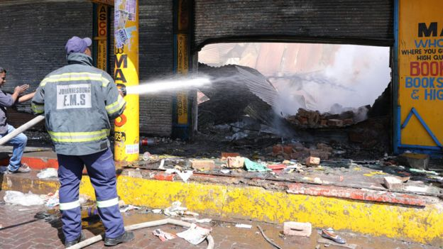 A shop keeper watches as a fireman douses down a burned and damaged property after overnight unrest and looting in Alexandra township, Johannesburg
