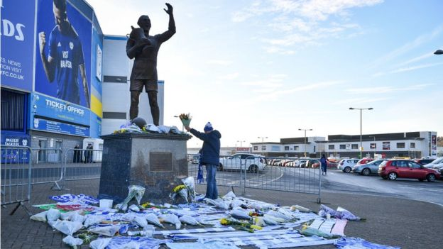 A fan lays flowers by the statue of Cardiff City footballer Frederick Charles Keenor outside Cardiff City Stadium