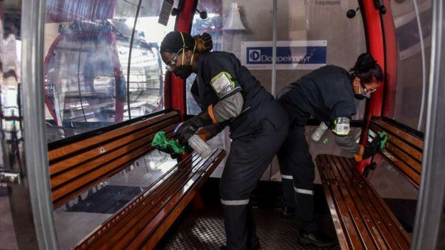 Mujeres limpian el interior del metrocable en Medellín