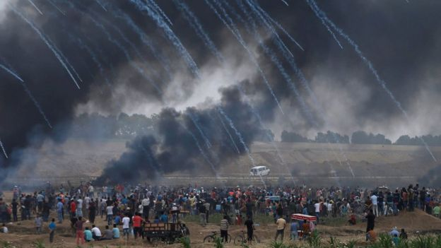 Tear-gas canisters are fired by Israeli troops towards Palestinians protesting on the Gaza-Israel border on 4 May 2018