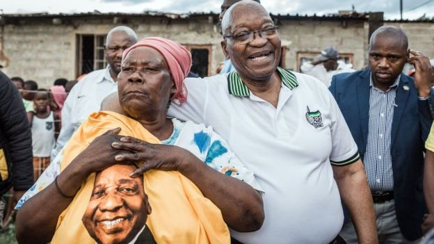Jacob Zuma (2ndR) is held tightly by ANC supporter Maria Mandweni during a door to door campaign visit in Shakaskraal township, on April 16, 2019