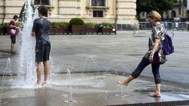 Personas refrescándose en fuentes de agua durante una ola de calor