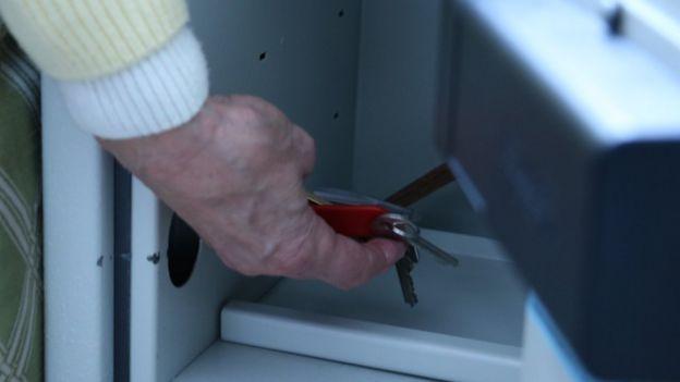Jackie poniendo sus llaves en una caja de seguridad.