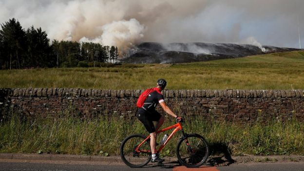 cyclist watches progress of fire from the road