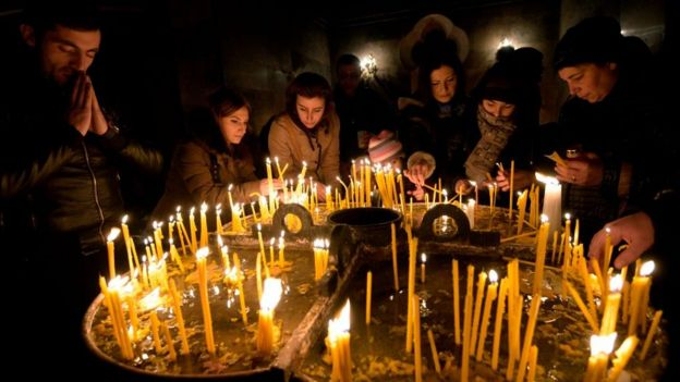 Armenians light candles on the eve of Orthodox Christmas inside a cathedral in Yerevan on 5 January 2018