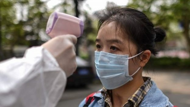 "A man wearing a protective suit checks a woman's temperature next to a residential area in Wuhan, in China""s central Hubei province on April 7, 2020."