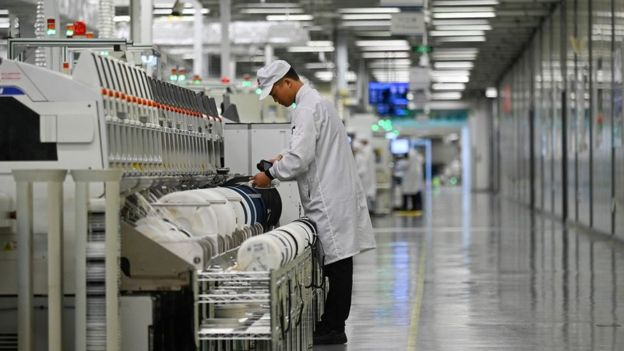 An employee works on a mobile phone production line at a Huawei production base during a media tour in Dongguan,
