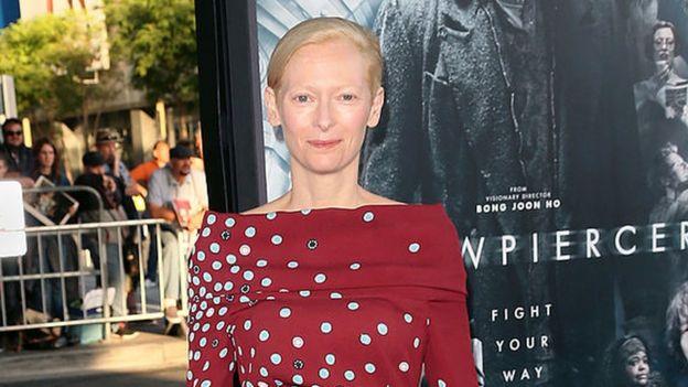 """Tilda Swinton frente a un afiche de """"Snowpiercer"""" durante el estreno de la película"""