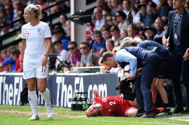 Mujer cae en una cancha de fútbol.