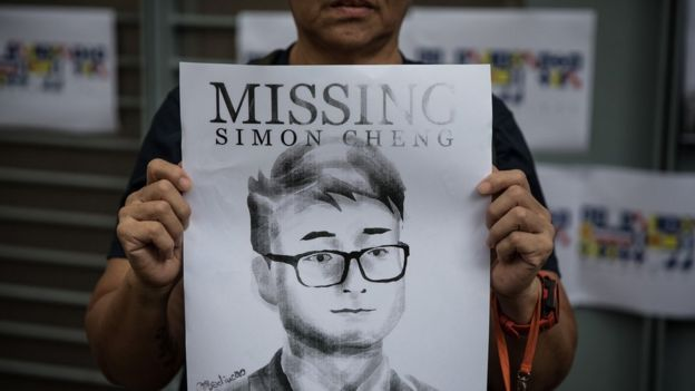 A woman holds a poster showing a portrait of British consulate worker Simon Cheng, who was detained