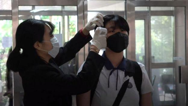 Una funcionaria toma la temperatura de un estudiante en una escuela de Seúl, Corea del Sur