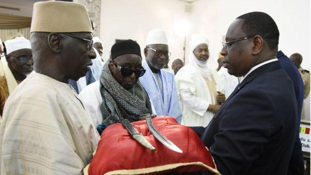 Le guide suprême des tidjanes du Sénégal, Serigne Babacar Sy Mansour (au premier rang, à gauche) et le président Macky Sall autour du sabre d'El Hadj Omar Tall.