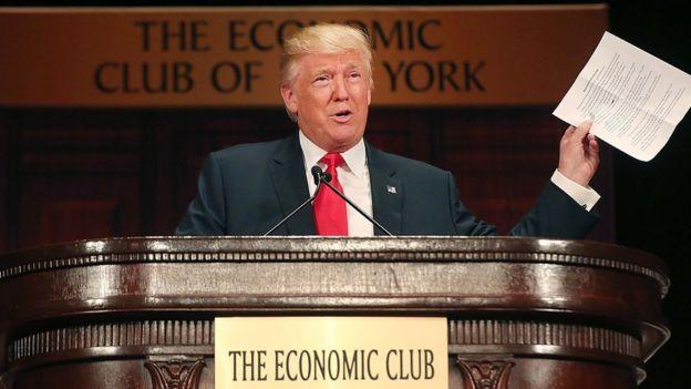 Trump frente a un estrado que Dice