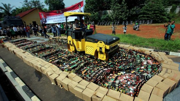 A bulldozer destroys bottles of illegal alcohol in South Tangerang, Indonesia (April 2018)