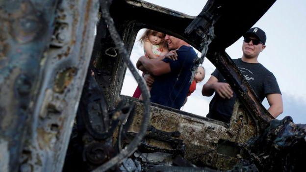 Parentes das vítimas choram ao ver o carro que explodiu durante o ataque