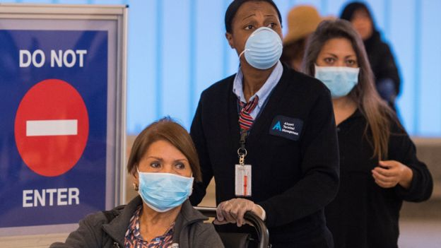 People wear face masks after arriving at the LAX airport in Los Angeles on 5 March 2020