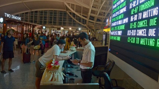 Passengers wait for flight information at Ngurah Rai airport in Bali
