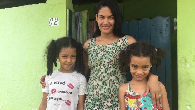 Maria Aparecida sorri abraçada com suas duas filhas, em frente a portão de casa