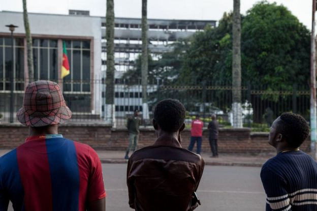 People look at the damaged building of Cameroon's parliament on November 17, 2017 in Yaounde, after a fire swept through the main building overnight, causing substantial damage.