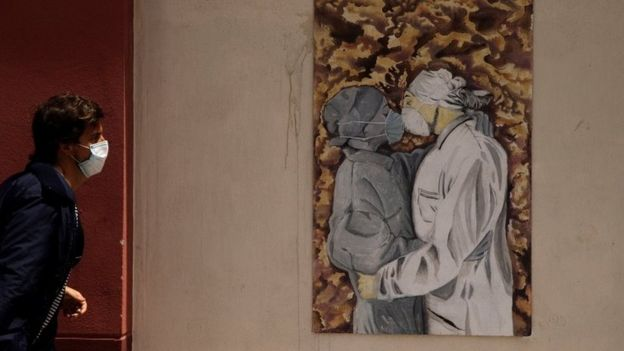 Man walks past painting in which people kiss in mask