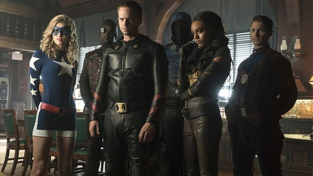 Legends of Tomorrow actors: (L-R): Sarah Grey as Stargirl, Kwesi Ameyaw as Dr Mid-Nite, Patrick J Adams as Hourman, Dan Payne as Obsidian, Maisie Richardson-Sellers as Amaya Jiwe/Vixen and Matthew MacCaull as Commander Steel