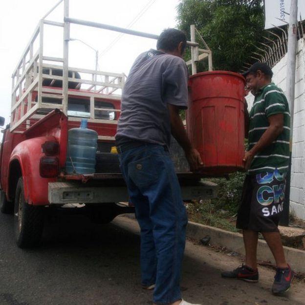 Homens carregam caminhão com água em Maracaibo