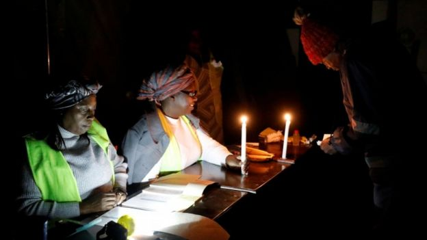 """Election officials sit at the table after providing a voter with ballot paper during country""""s general elections in Harare, Zimbabwe, 30 July 2018"""