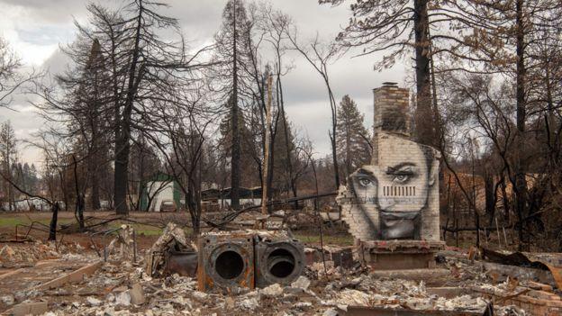 Casas destruidas por los incendios forestales en Paradise, California. En un muro se ve un grafiti con el rostro de una joven.