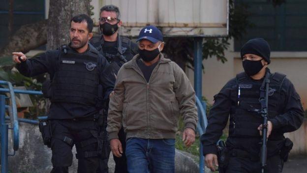 Queiroz caminha rodeado de policiais, todos de máscara